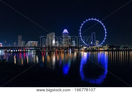 SINGAPORE - MARCH 22 2017: Night shoot of skyline with skyscrapers and Singapore Flyer.