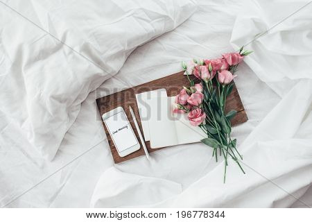 Wooden tray with paper sketchbook, smartphone and spring flowers on clean white bedding. Good morning concept.