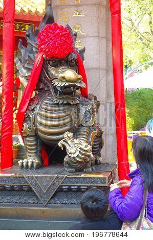 HONG KONG, CHINA - JANUARY 22, 2017: Unidentified people touching and looking a beautiful dragon statue made of bronze at Wong Tai Sin temple in Hong Kong, China.