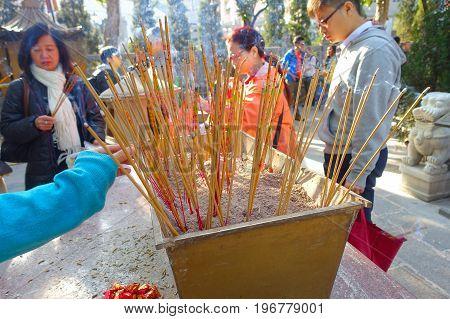 HONG KONG, CHINA - JANUARY 22, 2017: Close up of incenses burning up, with people behind of Wong Tai Sin Buddhist Temple to pray, in Hong Kong, China.