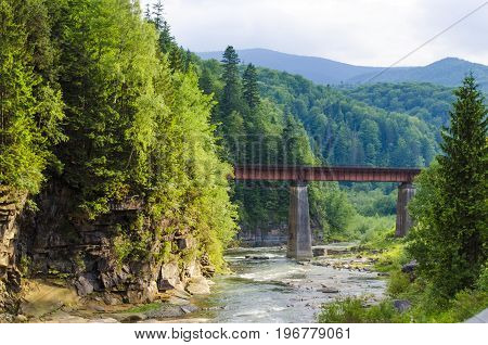 picturesque place, a mountain river with a rapid current of rocks and a bridge