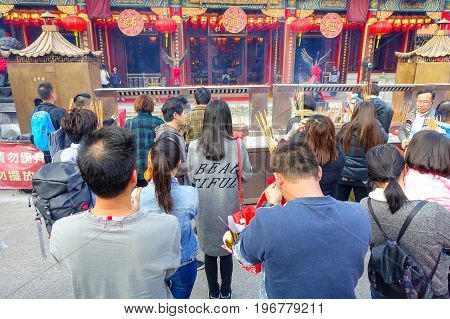 HONG KONG, CHINA - JANUARY 22, 2017: Crowd of people holding a their hands an incense sticks and praying inside of Wong Tai Sin Buddhist Temple to pray, in Hong Kong, China.