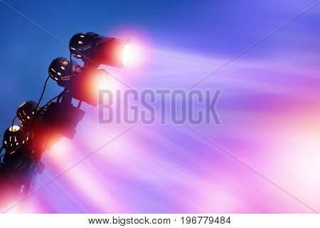 colorful lighting from spotlights for outdoor stage of a festival with twilight sky