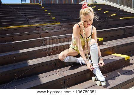 Very Beautiful sexy blonde girl posing on a vintage roller skates on a warm summer evening. Rollers quads . Outdoor.