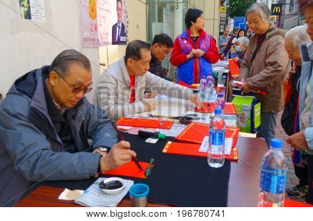 HONG KONG, CHINA - JANUARY 26, 2017: Unidentified people writting wisshes over a red paper contain meaning for Chinese New Year wishes in Hong Kong.