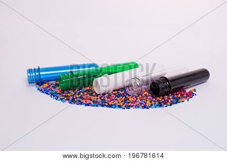 Clear Pet Preforms On White Background For Presentation. Preforms And Raw Materials Of Different Col