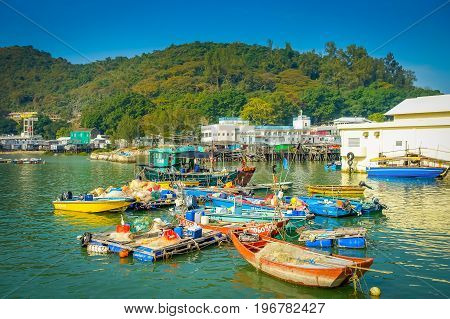 HONG KONG, CHINA - JANUARY 26, 2017: Riverboats in dirty river of old fishermen village Tai O with rustic houses, in a beautiful sunny day in Hong Kong.
