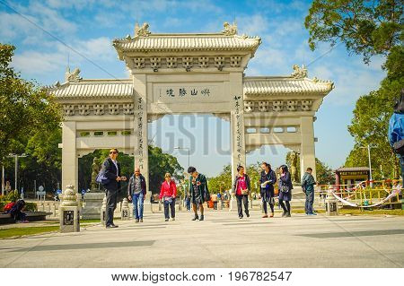 HONG KONG, CHINA - JANUARY 26, 2017: Unidentified people walking in the entrance gate to Tian Tin monastery and the Big Buddha at the Po Lin Monastery, Lantau Island, Hong Kong.