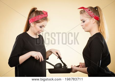 Preparing food concept. Retro styled girls trying to do something to eat on frying pan. Women cooking dinner making sauce pasta.