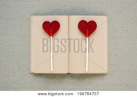 Two heart-shaped lollipops placed on an old diary on cloth background.