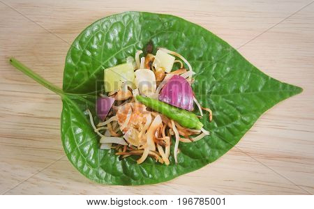 Thai Traditional Snack and Dessert Dish of Miang Kum or Sweet and Spicy Betel Leaf Wrap Filled with Coconut Peanuts Dried Shrimp Chiles and Lime.