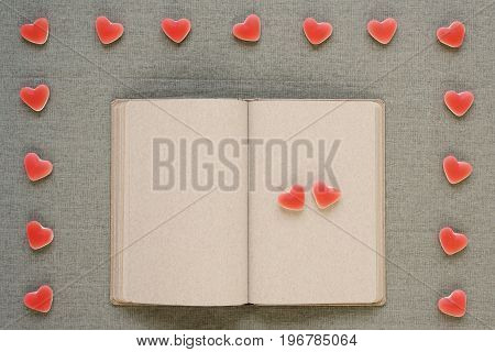 Fruit candies like little hearts placed on and around an old diary with empty pages.
