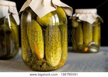 Closed glass transparent jar with fresh pickled cucumbers on black background, homemade preserved vegetables.
