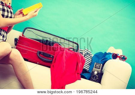 Packing for journay traveling concept. Girl sitting on couch with suitcase and full of things ready to be taken on summer holiday holds sunblock cream on blue