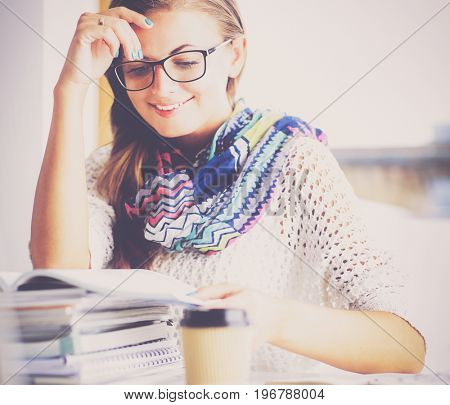 Young woman sitting at a desk among books