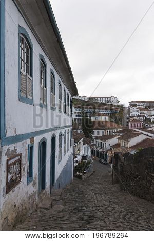 Ouro Preto is a colonial town in the Serra do Espinhaço mountains of eastern Brazil. It's known for its baroque architecture including bridges fountains and squares and its steep winding cobbled streets. Central Tiradentes Square is named after the martyr
