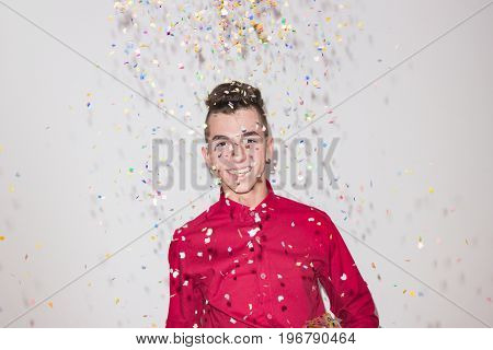 One Teenager Smiling, Looking To Camera, Red Shirt, White Background Studio, Confetti Party, Cheerfu