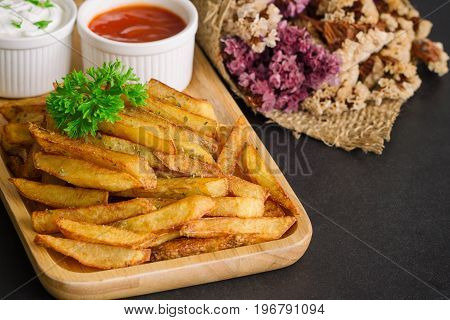 Homemade french fries serve with ketchup and sour cream or mayonnaise. Golden brown crispy french fries sprinkle with salt and oregano on plate for snack or appetizer. French fries on granite table with copy space. Delicious french fries.