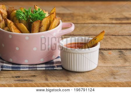 Homemade french fries serve with ketchup and sour cream. Golden brown crispy french fries sprinkle with salt and oregano on bowl for snack or appetizer. French fries on wood table. Delicious french fries on wood table with copy space.