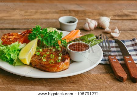 Barbecue pork steak on white plate served with barbecue sauce and vegetables. Pork steak for lunch or dinner on wood table. Moist and soft homemade pork barbecue served with mash potato and vegetable. Pork barbecue or steak ready to served.