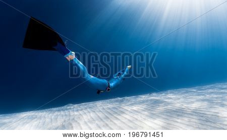 Woman freediver glides over sandy sea bottom