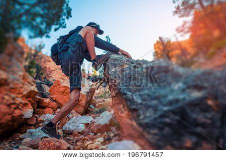 Hiker climbs rocky steep terrain