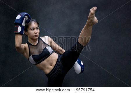 Young Asian woman boxer with blue boxing gloves kicking in the exercise gym Martial arts on black background