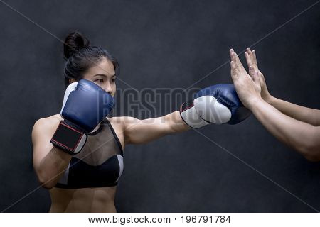 Young Asian woman boxer with blue boxing gloves punching to her trainer's hand in training gym Martial arts on black background