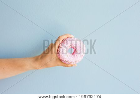 Woman holding pink delicious donut on blue background.