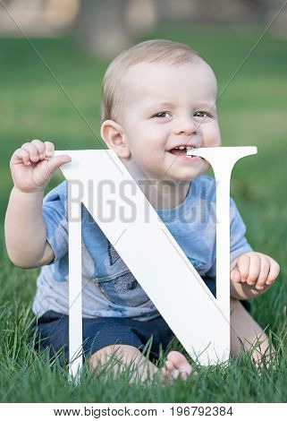 baby boy playing with big white letter N and scratching gums on green grass