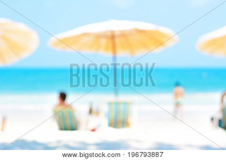 Blurred blue sea and white sand beach with parasols beach chairs and some people - holiday and vacation background concept