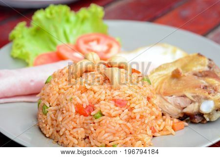 Thai food - fried rice with mixed vegetables and Cashew nuts serve with ham fried chicken and eeg (called Kaw Pad American or American fried rice)