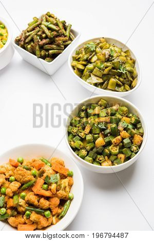 group photo of indian popular green vegetable food curries or sabzi or sabji like cauliflower/phool gobi, bhindi or okra, gawar or cluster beans, french beans, cabbage or patta gobi, flat green beans
