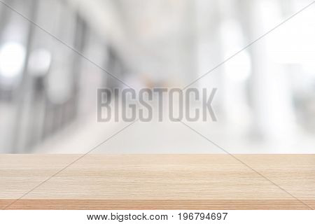 Wood table top on blurred white gray background of building hallway