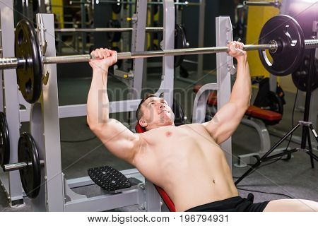 Weightlifter at the bench press lifting a barbell on an incline bench poster