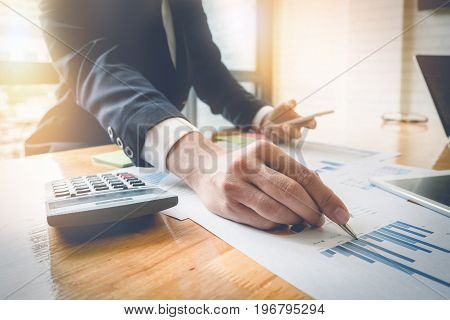 Close Up Business Man Holding Pen And Point To Data Sheet While Using Smartphone And Calculator For