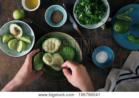 Cooking of Mexican guacamole sauce. Man preparing Mexican sauce guacamole on rustic wooden table top view top view