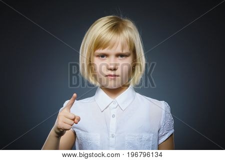 displeased angry girl with threatens finger isolated on gray background.