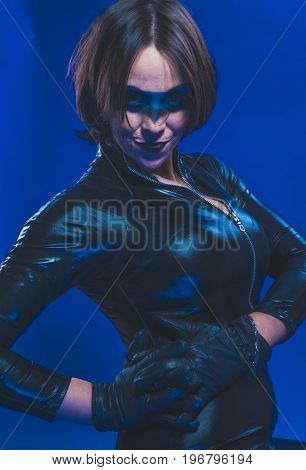 Agent, Brunette girl dressed in leather and latex fitted with pistol on blue background