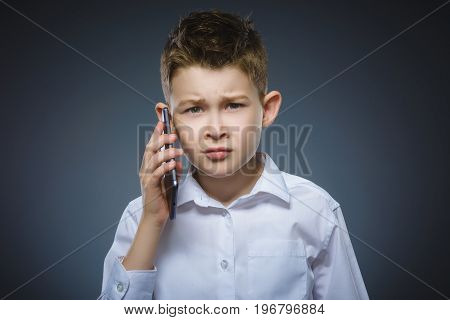 Portrait of offense boy with mobile or cell phone. Negative human emotion, facial expression. Closeup.
