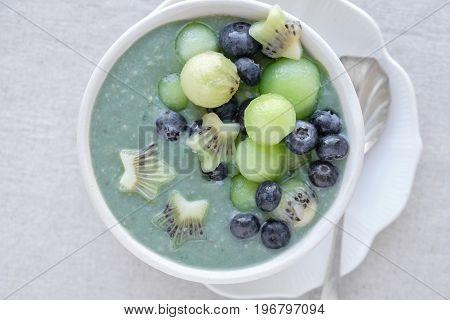 Blue spirulina smoothie bowl with melon kiwi fruit and blueberries