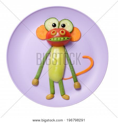 Funny vegetable ape made on pink plate;