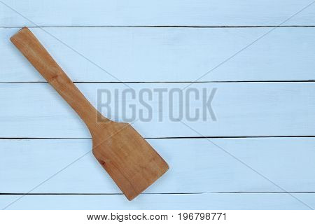 wooden ladle on blue wood background for design in your work.
