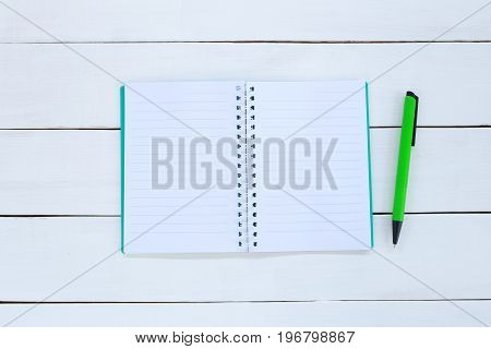 Book and pen on white wood background for design in your work educational concept.