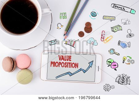 Value Proposition, Business Concept. Mobile phone and coffee cup on a white office desk.