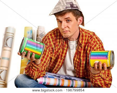 Repair home man holding paint can. Tired and frustrated mad male in newspaper cap renovation apartment. Painting walls for money. Worker-builder student. Choice of materials for construction.
