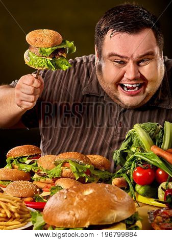 Fat man who makes choice between healthy and unhealthy food. Poor food leads to obesity idea. Black background.