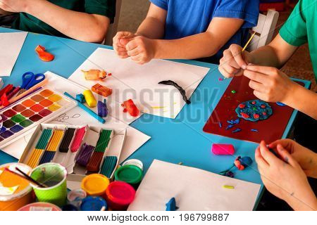 Plasticine modeling clay in children class. Teacher teaches kids together play dough and mold from plasticine in kindergarten or preschool. Development of fine motor skills of fingers.