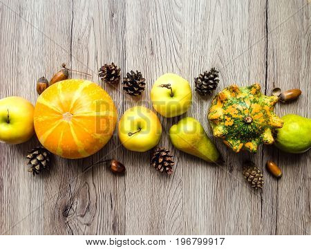 Stylish composition of colorful vegetables fruits autumn natural elements: acorns cones. Top view on wooden background. Autumn flat lay border