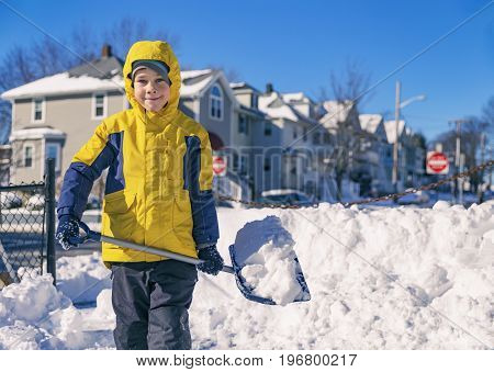Smiling boy is carrying snow on a shovel. Child cleans the yard after a snowfall. Kid shoveling snow